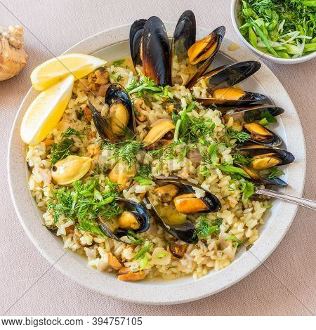 Mediterranean Dish - Risotto, Pilaf With Mussels In A Plate With Lemon Slices And Parsley Close-up,