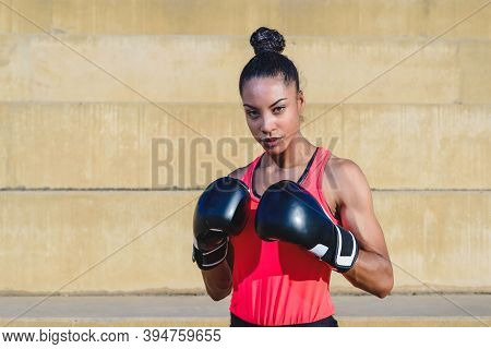 Horizontal Portrait Of An Attractive African Woman Wearing Sport Clothes And Boxing Gloves Standing