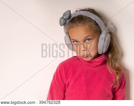 Little Cute Girl Blowing Sponges Offended In Warm Fur Headphones On A Light Background