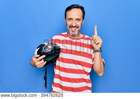 Middle age handsome motorcyclist man holding moto helmet over isolated blue background smiling with an idea or question pointing finger with happy face, number one