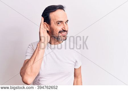 Middle age handsome man wearing casual t-shirt standing over isolated white background smiling with hand over ear listening and hearing to rumor or gossip. Deafness concept.