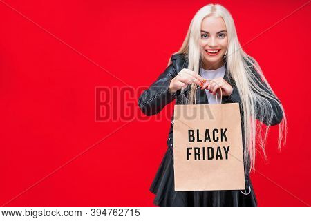 Beautiful Smiling Blonde Girl Is Holding Paper Bag Pack. Stylish Fashionable Woman In Leather Clothe