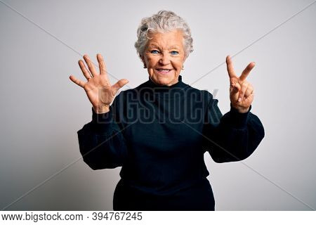 Senior beautiful woman wearing casual black sweater standing over isolated white background showing and pointing up with fingers number seven while smiling confident and happy.