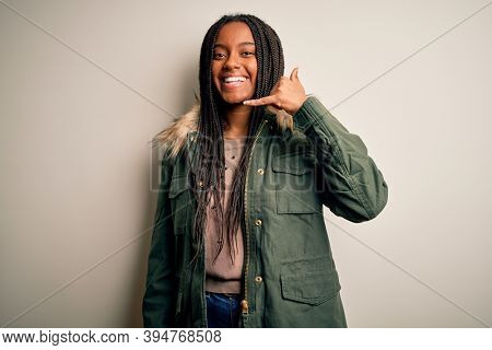 Young african american woman wearing winter parka coat over isolated background smiling doing phone gesture with hand and fingers like talking on the telephone. Communicating concepts.