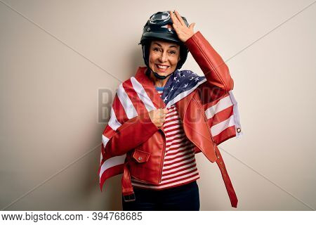 Middle age motorcyclist woman wearing motorcycle helmet and united states flag stressed with hand on head, shocked with shame and surprise face, angry and frustrated. Fear and upset for mistake.