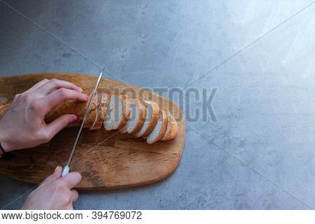 Flat Tabletops And The Process Of Slicing A Long Baguette. Female Hands Gently Cut Fresh Bread With