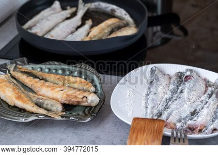 Freshly Caught Sea Fish Smelt Lies In A Plate With Flour, Fried In A Plate And Fried In A Pan, The P