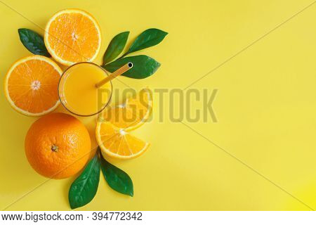 Composition Of Oranges, Slices, Glass With Metal Steel Straw, Leaves Are Laid Out On Left Side Of Ye