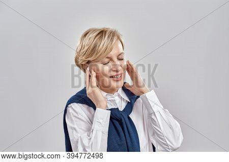 Portrait Of Elegant Middle Aged Caucasian Woman Wearing Business Attire, Adjusting Her Earbuds, Enjo