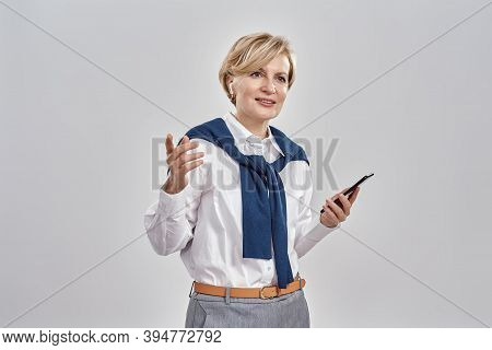 Portrait Of Elegant Middle Aged Caucasian Woman Wearing Business Attire And Earphones Holding Smartp