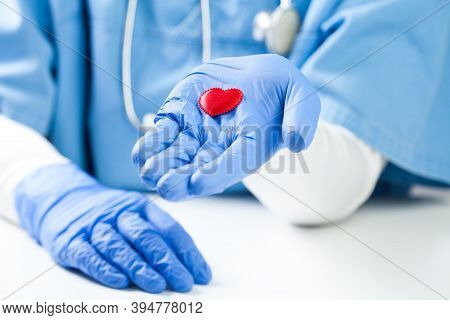 Female Doctor Holding Small Red Heart On Palm Of Hand, Wearing Blue Nhs Uniform, Detail Closeup, Fre