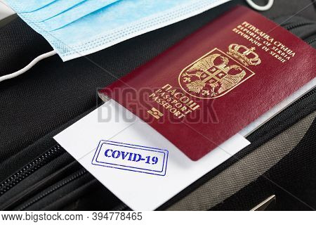 Passport And Medical Face Mask On A Suitcase, Paper With Covid-19 Stamped Onto It, Point Of Care Tes