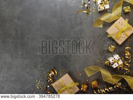 New Year Card. Craft Gifts With Gold Ribbon, Bright Streamer And Christmas Confetti On A Dark Backgr