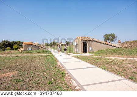 Tarquinia, Italy - 18 September 2020: Pedestrian Path With Tourists Between The Entrances To The Tom