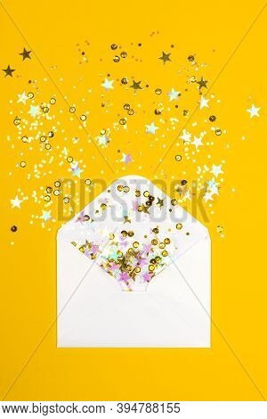 Sparkling Confetti Pouring Out Of White Envelope On Yellow Background. View From Above. Flat Lay. Ho