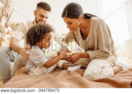 Happy Family Multi Ethnic Mother Feels Sorry For Baby Who Hurt The Leg In Bed In Bedroom At Home