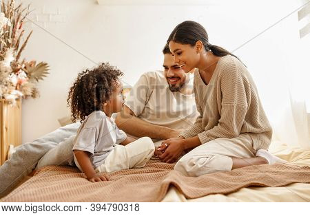 Happy Family Multi Ethnic Mother, Father And Son  Laughing, Playing,and Tickles In Bed In Bedroom At