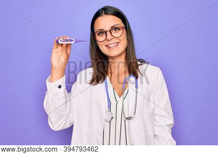 Young beautiful brunette doctor woman wearing stethoscope and coat holding thermometer looking positive and happy standing and smiling with a confident smile showing teeth