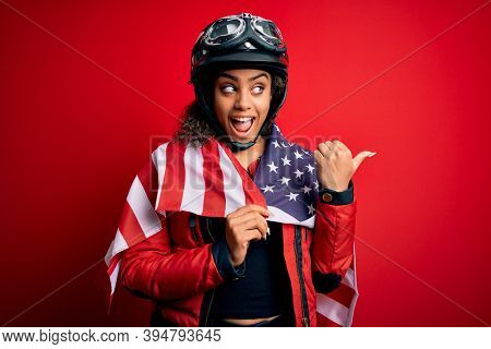 African american patriotic motorcyclist girl wearing moto helmet wearing united states flag pointing and showing with thumb up to the side with happy face smiling