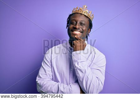 Young african american man wearing golden crown of king over isolated purple background looking confident at the camera with smile with crossed arms and hand raised on chin. Thinking positive.