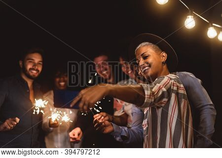 Happy Young Friends Celebrating New Year Eve With Sparklers Fireworks While Taking Selfie With Mobil