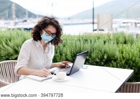 Young Woman Working In Opened Restaurant. Freelancer Wearing Protective Mask, Using Laptop In Empty