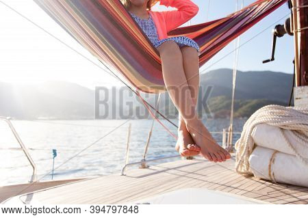 Kid Relaxing In Beach Hammock On Yacht. Little Girl Traveling In Summer Vacation. Close Up Of Legs A