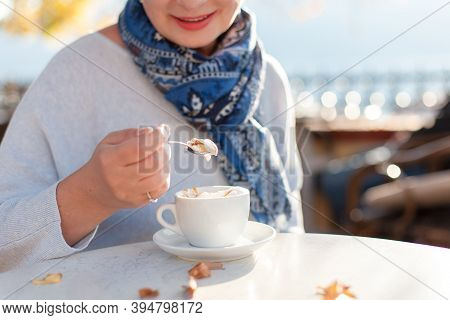 Senior Woman Drinking Coffee In Autumn Cafe Outdoors. Retired Person Eating Coffee Cream With Carame