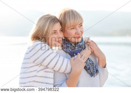 Mother And Adult Daughter Hugging. Happy Young And Senior Women Together On Sea Beach. Concept Of Te