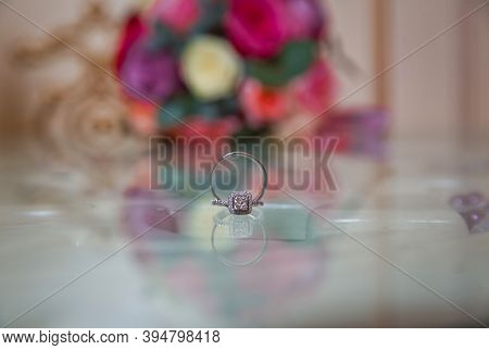 Glass Table . Wedding Rings Next To A Red Flower Bouquet Selective Focuse . Bride And Groom With Eng