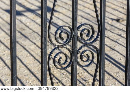 Black Wrought Iron Fence Bars With Curled Pieces Against A Dirt Background