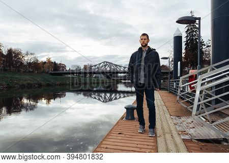 Portrait Of Young Caucasian Man In Jacket Walking On Shipyard On Vltava River. Ceske Budejovice, Cze