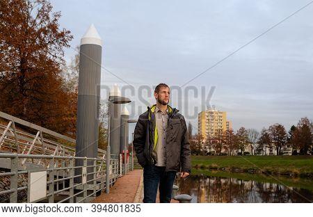 Half Portrait Of Young Caucasian Man In Jacket Walking On Shipyard On Vltava River. Ceske Budejovice