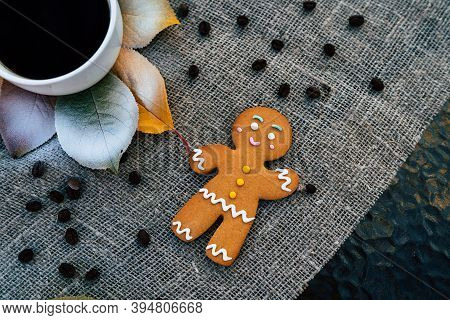 Gingerbread Man And Cup Of Coffee Near Autumn Leaves. Top View Of Sweet Gingerbread Man And Cup Of S