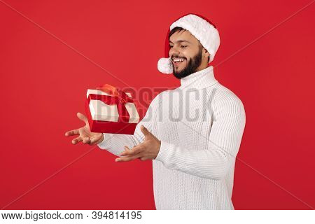 Funny Hipster Man Wears Santa Claus Hat Cathing Flying Gift Box Over Red Background. Christmas And N