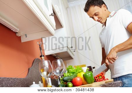 Portrait of young man cutting vegetables in the kitchen