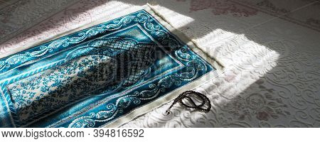 Prayer Rug For Praying In Islam, Prayer Rug And Rosary Laid Under Daylight,