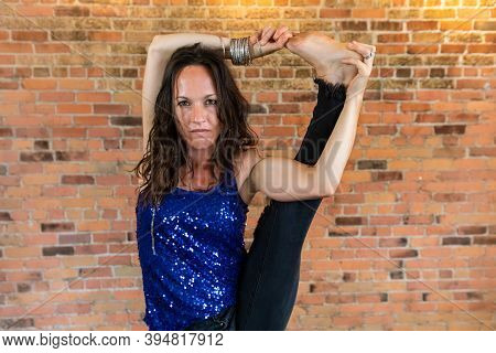 A Strong And Empowered Woman Looks Directly Into The Camera, As She Stands In An Advanced Pose With
