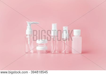 Set Of Empty Travel Women Toiletries Beauty Kit On Pink Orange Background. Approved For Airplane Lug
