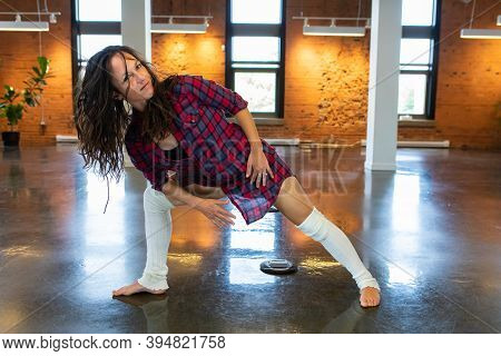 A Front, Full Length Shot Of A Woman Wearing A Red Plaid Shirt And White Leg Warmers As She Moves Th
