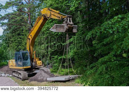 Selective Focus, An Excavator In The Park Lays Concrete Slabs. Paving The Sewer Line. Construction E