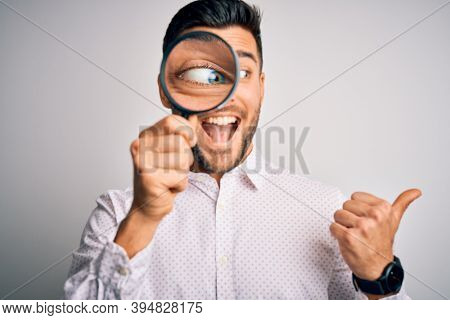 Young detective man looking through magnifying glass over isolated background pointing and showing with thumb up to the side with happy face smiling