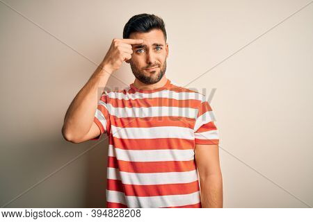 Young handsome man wearing casual striped t-shirt standing over isolated white background pointing unhappy to pimple on forehead, ugly infection of blackhead. Acne and skin problem