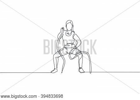 Single Continuous Line Drawing Of Young Sportive Woman Training With Battle Rope In Sport Gymnasium