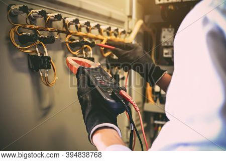 Close-up Hand Of Electrical Engineer Holding Measuring Equipment To Checking Electric Current Voltag