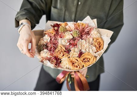 Beautiful Bouquet Of Mixed Flowers In Womans Hands. The Work Of The Florist At A Flower Shop. Delive