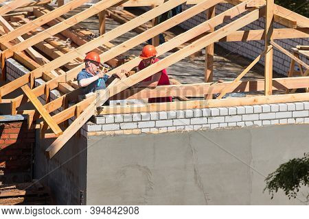 Grodno, Belarus - June 2020: Two Workers Roofers In Helmets Surrounded By Rafters And Beams At Const