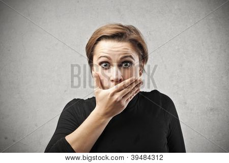 Astonished woman covering her mouth with her right hand