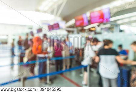 Blurred Airport Check-in Counters With Passengers And Crowd Control Barriers.travel And Transportati