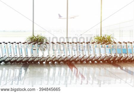 The Row Of Empty Luggage Trolley In The Airport With An Airplane Taking Off In The Morning. Travel A